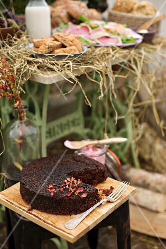 An autumnal buffet in a garden with a beetroot cake, rolls and a meat platter