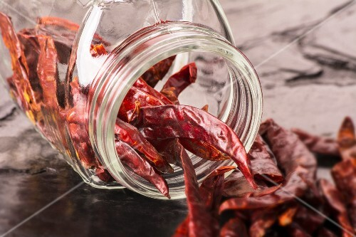Dried chilli peppers spilling from an overturned storage jar