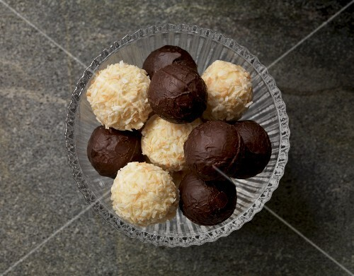 White and dark chocolate truffles in a glass bowl