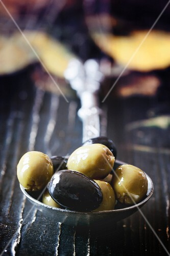 Black and green olives on a vintage spoon