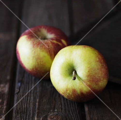 Two apples on a rustic wooden surface