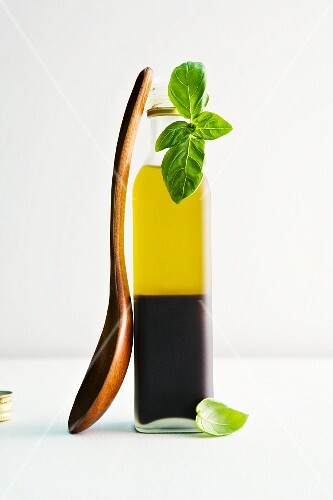 A bottle of vinegar and oil with basil and a wooden spoon