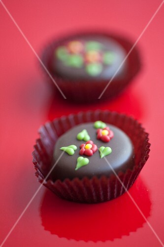 Two chocolate pralines with sugar decorations