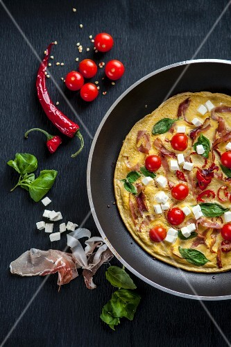 A breakfast omelette with tomatoes, feta cheese, ham and basil