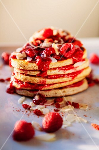 A stack of pancakes with raspberries and slivered almonds