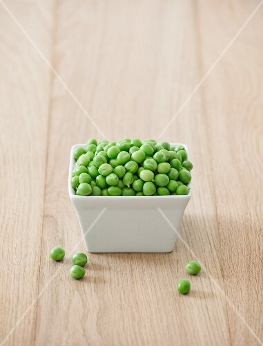 A bowl of fresh peas on a wooden table