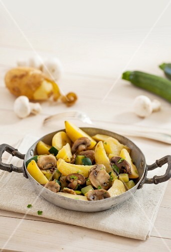 Potatoes with courgettes and mushrooms in a pan