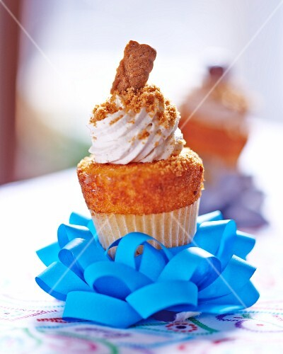 A cupcake topped with cream on a decoratively folded ribbon