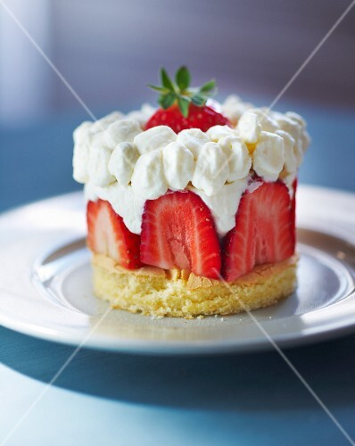 A sponge cakes with fresh strawberries and cream