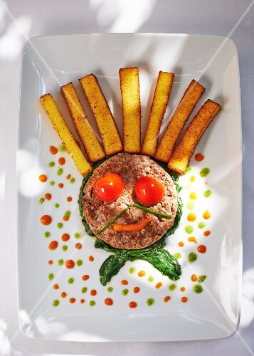 A funny face made from minced meat and polenta sticks