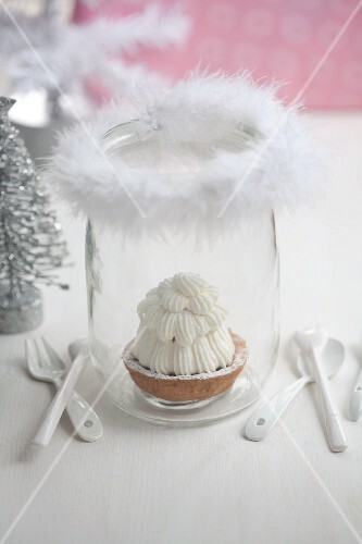 A shortcrust tartlet in a glass decorated with a feather