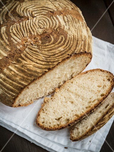 A freshly baked homemade loaf of wheat sourdough bread, sliced
