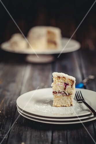 A slice of coconut cake on a stack of plates
