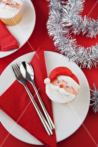 A Father Christmas cupcake on a plate with a napkin and cutlery