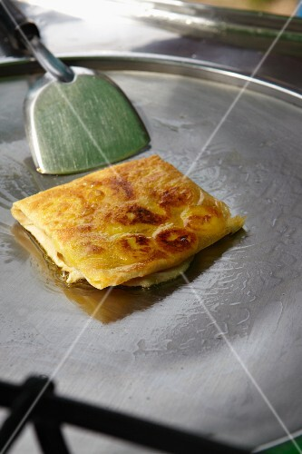 A banana crepe being made using a crepe maker