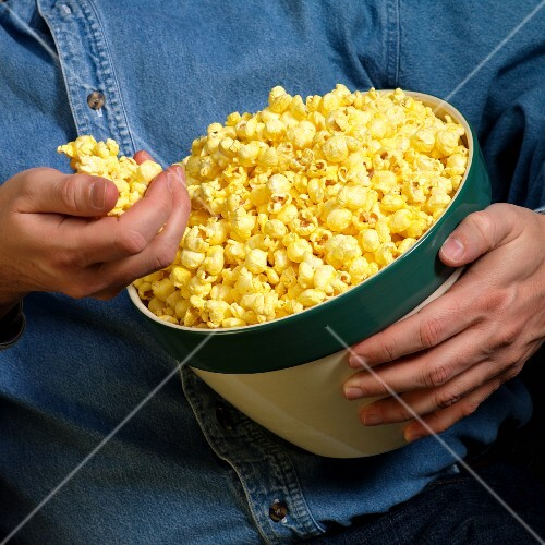 A man holding a bowl of popcorn