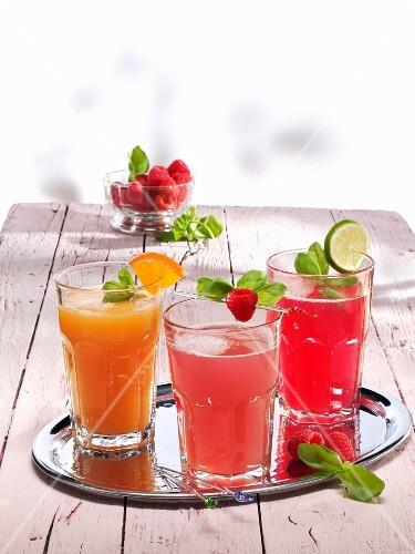 Three different glasses of lemonade (orange & raspberry, ginger & raspberry, and raspberry)