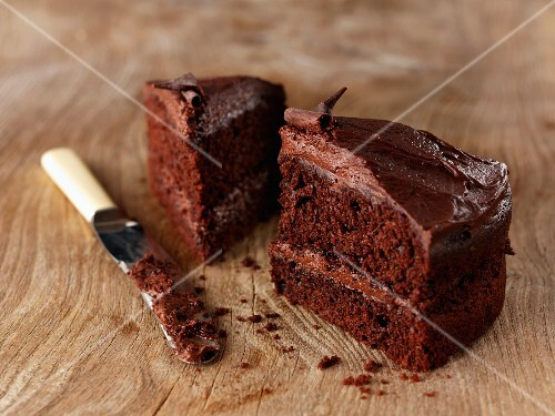 Two slices of chocolate cake with a knife on a wooden surface