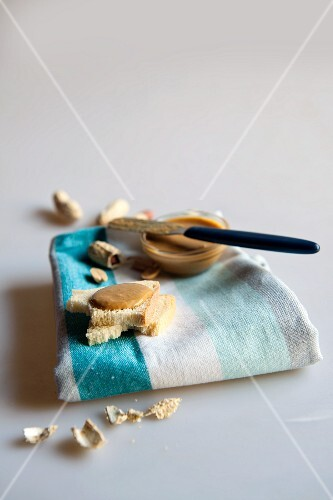 Toast with peanut butter on a tea towel with peanuts