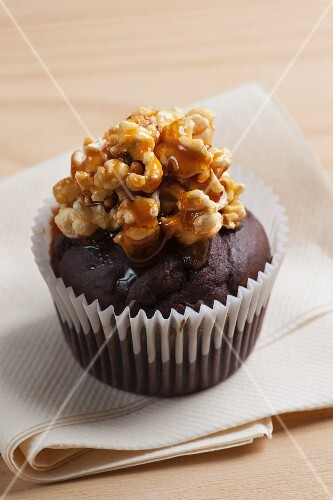 A chocolate cupcake topped with popcorn and caramel