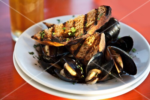 Mussels in a beer broth with garlic and herbs served with grilled bread