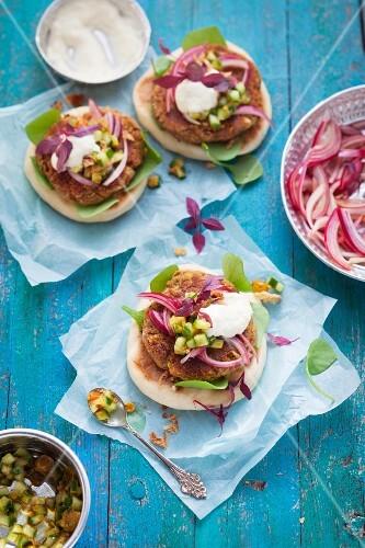 Kichererbsen-Burger auf Fladenbrot mit roten Zwiebeln, Gemüse- und Joghurtsauce