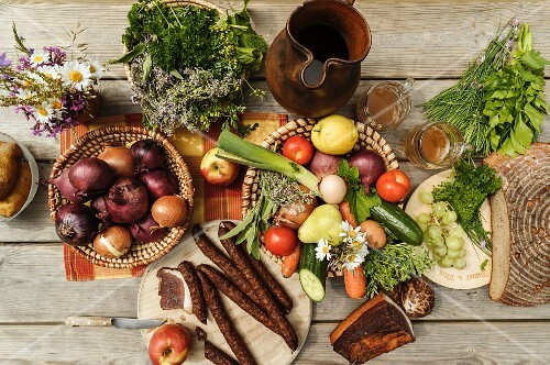 A bird's-eye view of a table laid with onions, a jug of must, vegetables, fruit, bacon, bread and snack sausages, Austria
