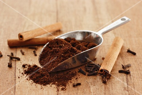 Coffee powder on a metal scoop between cinnamon sticks and cloves