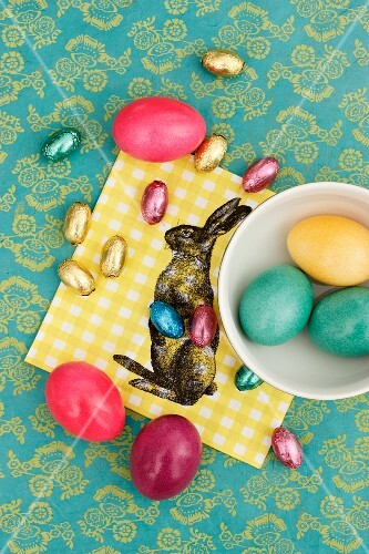 Easter eggs and chocolate eggs on a napkin decorated with an Easter bunny
