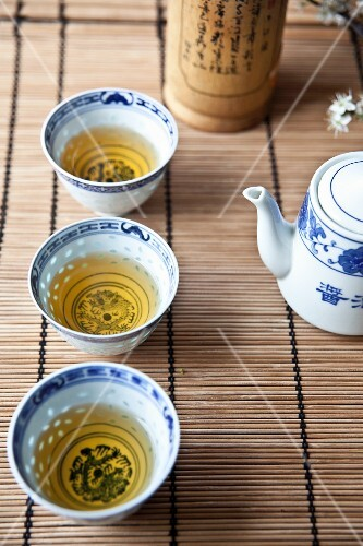 Three oriental tea bowls filled with green tea on a bamboo mat