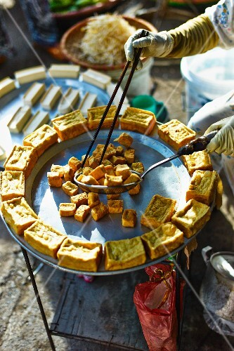 A woman selling fried tofu at a market in Haiphong, Vietnam