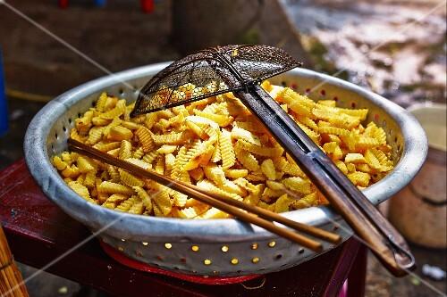Crinkle cut chips in an aluminium sieve at a market in Haiphong, Vietnam