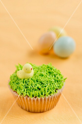 A vanilla cupcake decorated with grass and a chick for Easter