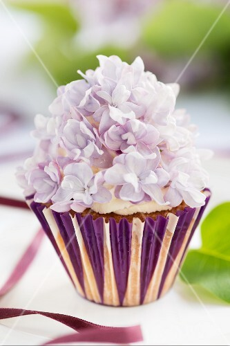 A cupcake decorated with lilac flowers