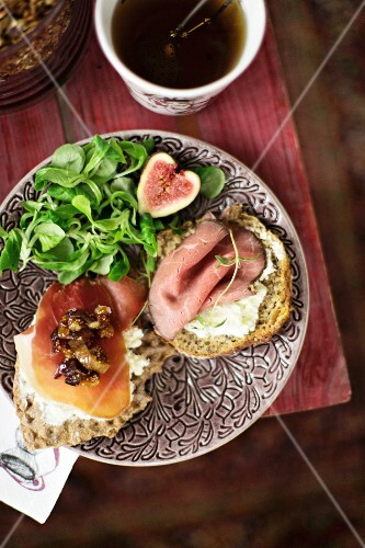 A bread roll topped with cream cheese, ham, dried figs and dates