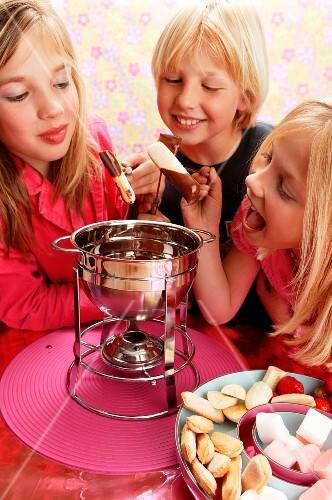 Children eating chocolate fondue