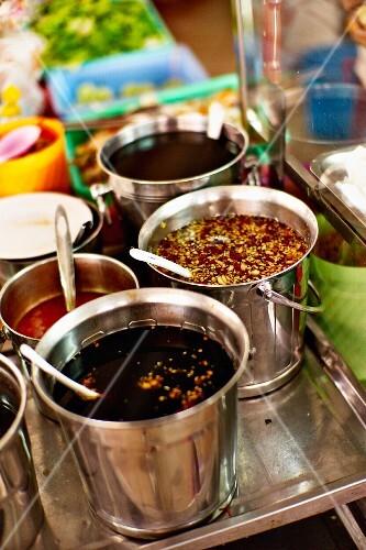 Various sauces in buckets at a market in Saigon (Vietnam)