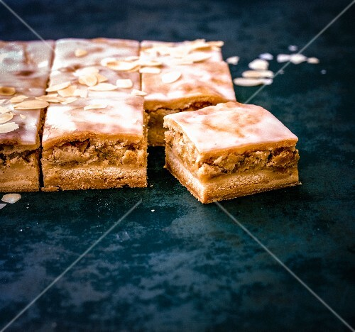 Apple pie tray bake with icing sugar and slivered almonds