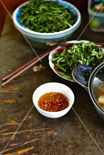 Chilli sauce in a small bowl with leafy vegetables, Vietnam