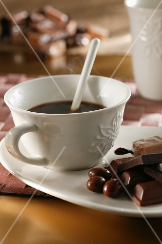A cup of black coffee with chocolate on the saucer