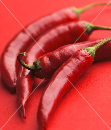 Four red chilli peppers on a red surface