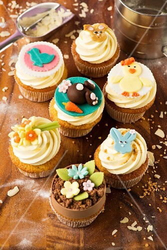 Various Easter cupcakes on a wooden table