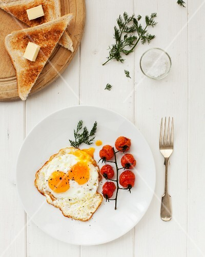 A fried egg with tomatoes and toast triangle with butter