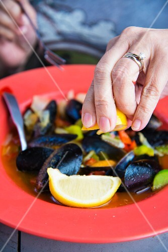 Mussels being drizzled with lemon juice