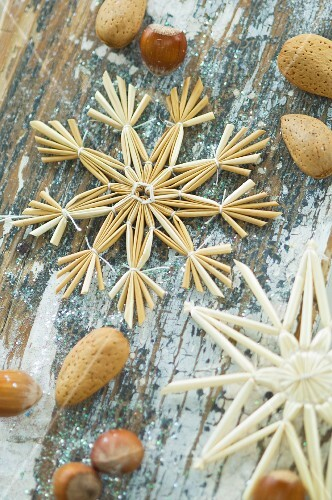 Christmas arrangement of straw star, hazelnuts and almonds on table