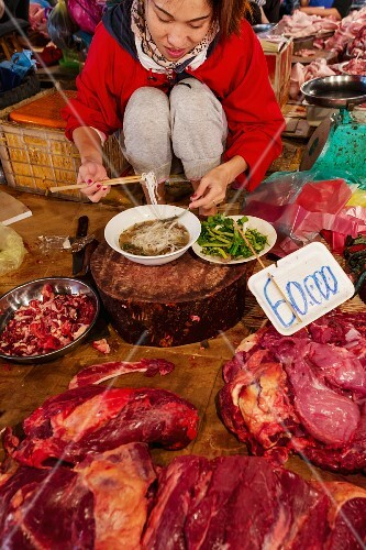 A young woman eating noodle soup at a market, Laos