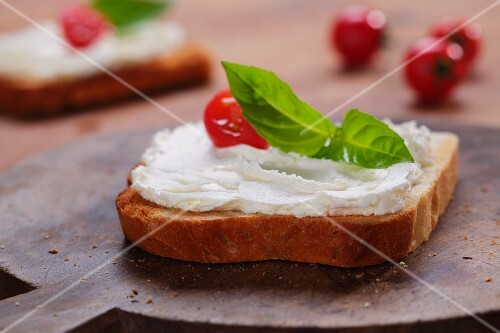 A slice of toast topped with cream cheese, tomato and basil