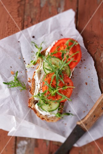 A slice of bread topped with cream cheese, cucumber, tomato and rocket