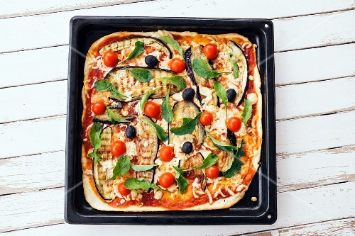 A pizza topped with grilled aubergines, tomatoes and olives on a baking tray