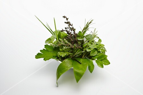 A bowl of fresh herbs against a white background